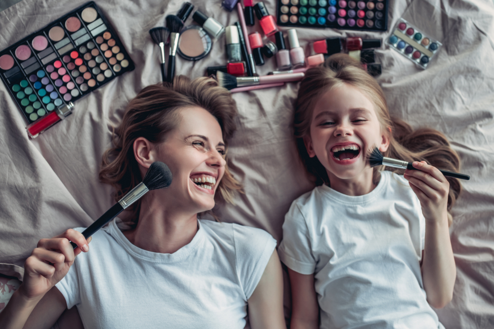 woman and child putting makeup on in bed